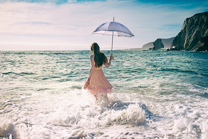 Girl with umbrella in the sea